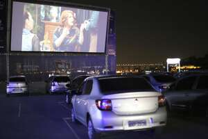 NITEROI, BRAZIL - JUNE 25: Moviegoers watch a film from their cars in the drive-in cinema at Caminho Niemeyer amidst the coronavirus (COVID-19) pandemic on June 25, 2020 in Niteroi, Brazil. The space has a capacity for up to 110 vehicles, and a 210 square meter state-of-the-art screen. At the drive-in entrance, an employee, wearing personal protective equipment (PPE), guides the public to the location of each vehicle. (Photo by Luis Alvarenga/Getty Images)