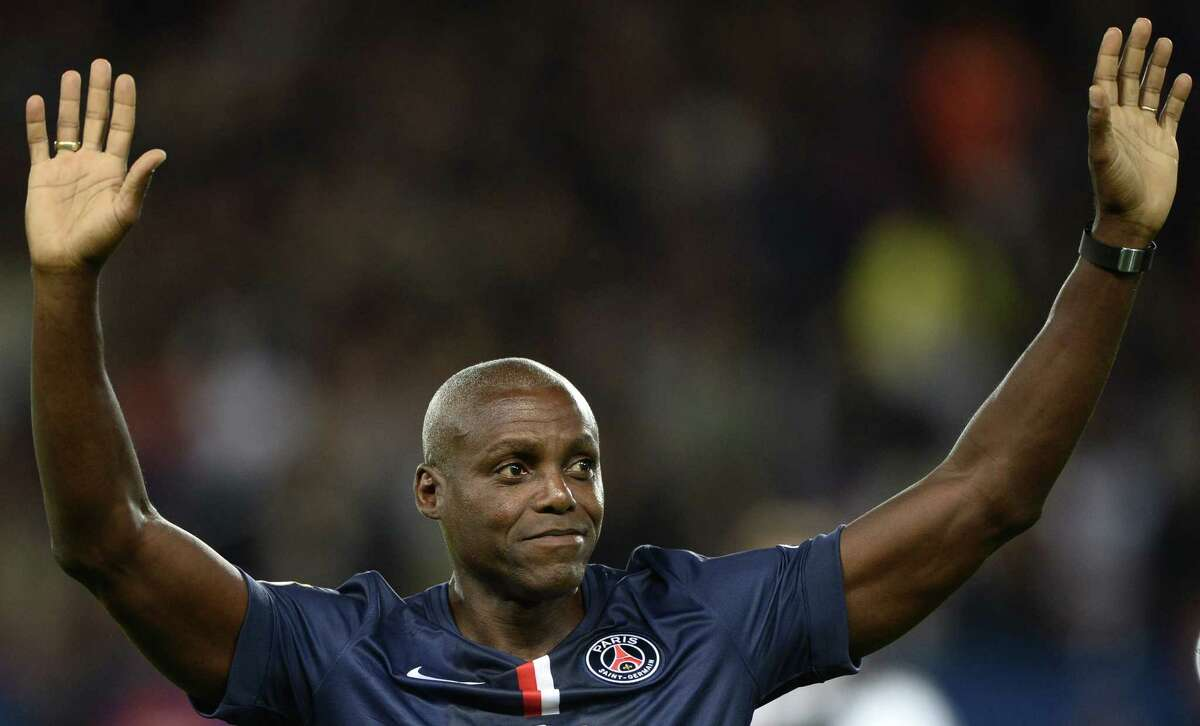 US sprint and long jump legend Carl Lewis acknowledges football fans before the start of the French L1 football match between Paris Saint-Germain (PSG) and Monaco at the Parc des Princes stadium in Paris on October 5, 2014. AFP PHOTO / FRANCK FIFEFRANCK FIFE/AFP/Getty Images ORG XMIT: 498985795