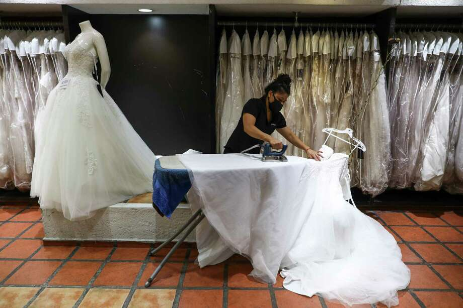 A woman wearing a mask to curb the spread of the new coronavirus irons a wedding dress at a store in Mexico City, Tuesday, June 30, 2020. Photo: Eduardo Verdugo, AP / Copyright 2019 The Associated Press. All rights reserved