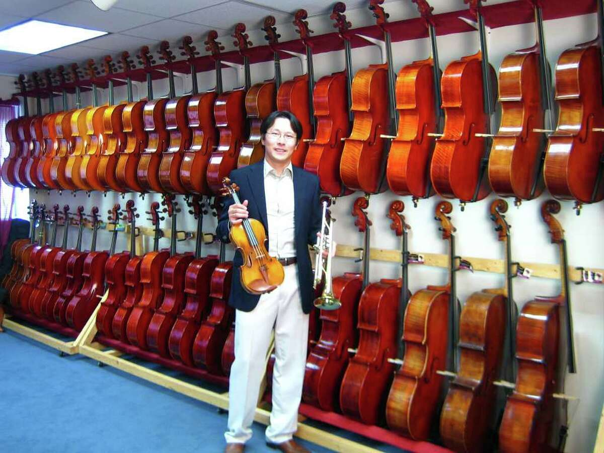 Kenneth Kuo, founder of Connecticut School of Music, stands in front of a row of cellos at the Connecticut School of Music in Westport. Kuo is launching a store in Greenwich as well.