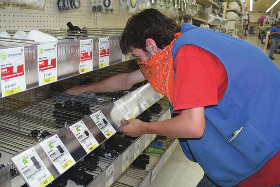 Clint Wade, 18, of Winchester cleans a shelf Tuesday at Midland Farm and Home Supply. Workers who make minimum wage, like Wade, are about to see a pay hike today. Photo: Marco Cartolano | Journal-Courier
