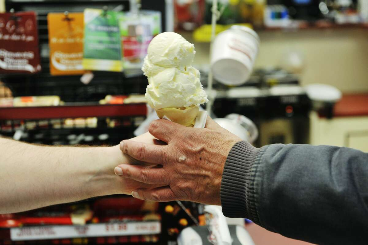 A customer grabs their ice cream cone at a Stewart's Shop.