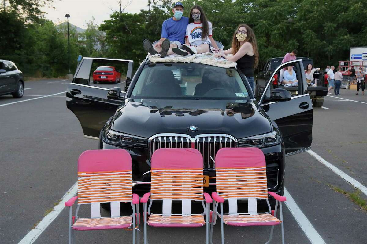 Getting a better seat are, from left, Jeff Hellinger of Weston, Sydney, and Deborah at the drive-in premiere of the new Remarkable Theater on Friday, June 27, 2020, in Westport, Conn.