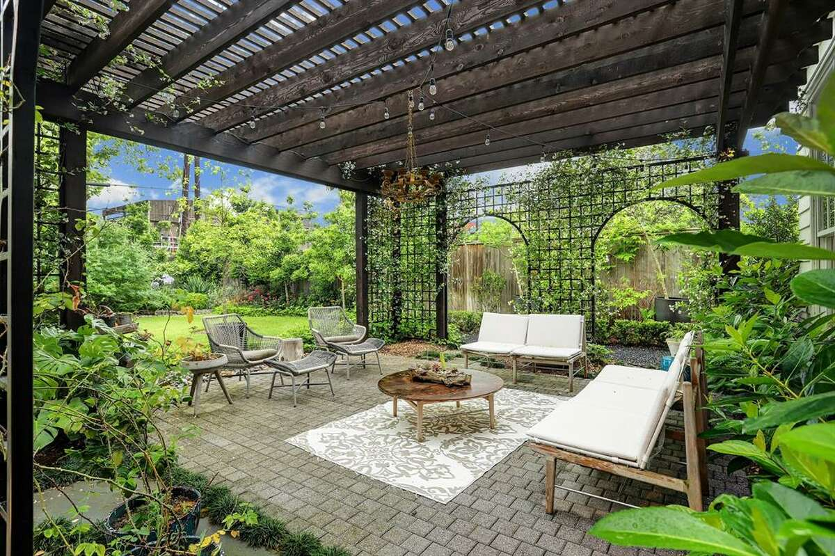 The backyard is outfitted with a beautiful pergola courtyard perfect for gardening enthusiasts.