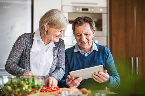 Old man and woman preparing meal inside, looking up a recipe on the internet.