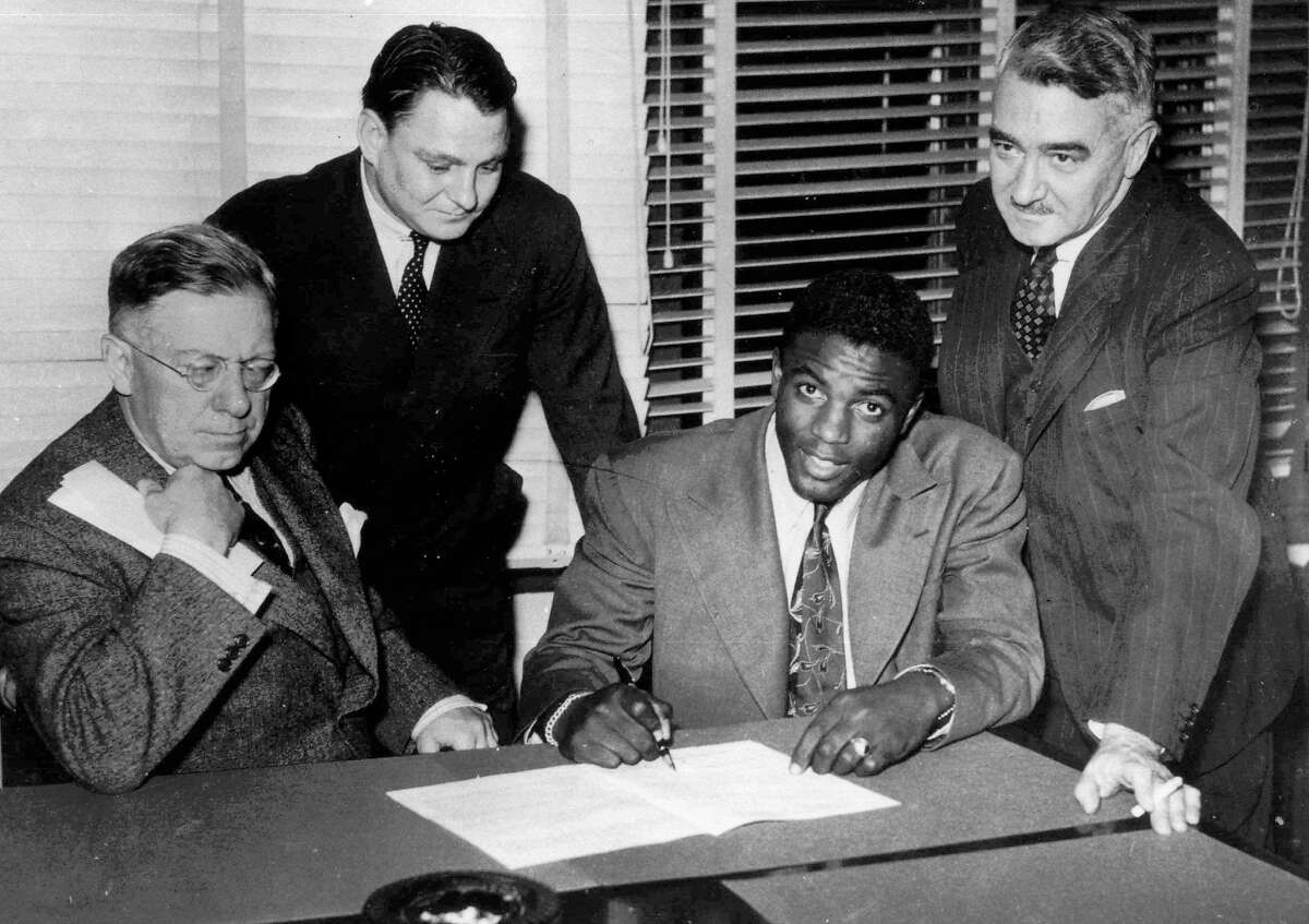FILE - In this Oct. 23, 1945, file photo, Jackie Robinson, first Negro player in the major leagues, signs with the Montreal Royals in Montreal. From left are: Royals president Hector Racine, Branch Rickey Jr., Robinson and Royals vice-president Romeo Gauvreau. Baseball's MVP award is engraved with the name of Kenesaw Mountain Landis, the first baseball commissioner. No Blacks played in the majors during his quarter-century tenure; Jackie Robinson broke the barrier about 2 1/2 years after Landis died. (AP Photo/File)
