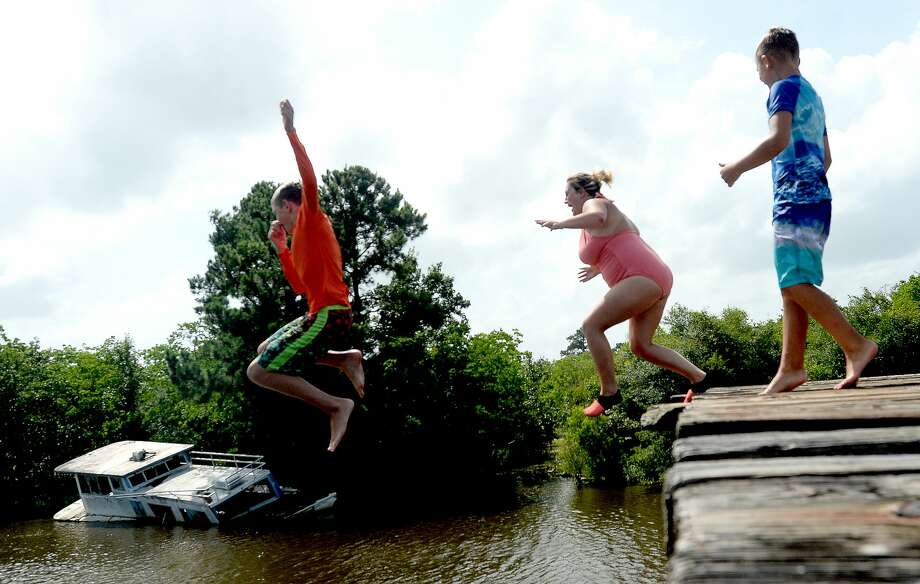 """Brody Lonion laughs as his mother Ashley Ply joins stepbrother Kaden Ply jumping from the old bridge that spans Cow Bayou near the boat launch beneath the Texas 87 bridge. Ashley Ply said jumping off the old bridge into the bayou is a long tradition for kids in the area. """"And especially now wtih places closed due to COVID-19, it's one of the only places kids have to swim"""" during hot summer days, she says. Ply remembers many days spent with friends when she was a teen making the over 20-foot jump, but it took some prodding from her sons to join them now. """"I used to do this all the time when I was 16,"""" she says, peering over the edge of the bridge to the water below. """"Wow, this is really high!"""" She didn't remember it looking that high when she was a teen, she said. Eventually, the boys' pleas for her to join them in just one jump, and promises of a back massage and manicure, won her over, and the three made the jump together. Photo taken Tuesday, June 30, 2020 Kim Brent/The Enterprise Photo: Kim Brent/The Enterprise"""