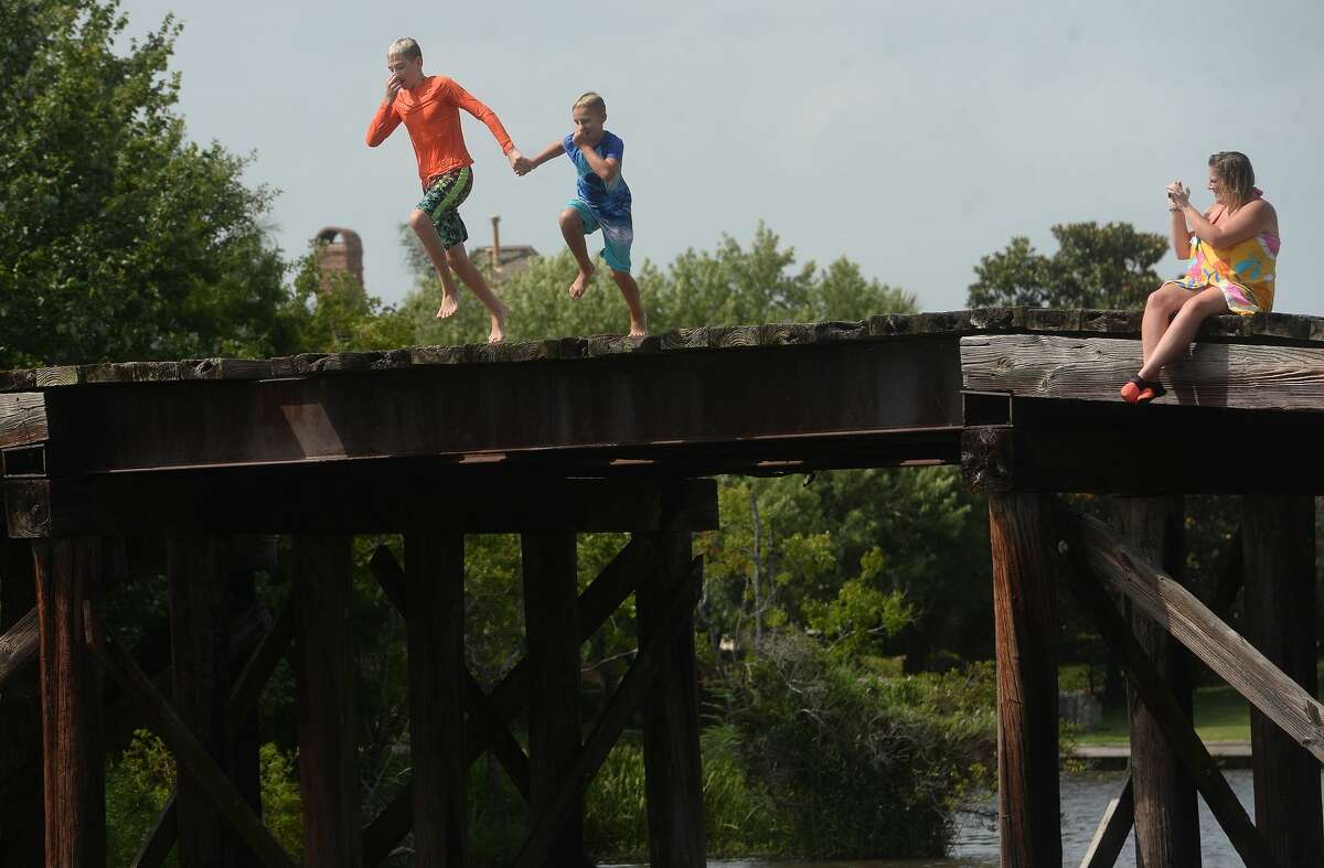 Brody Lonion and stepbrother Kaden Ply enjoy their first time of the summer swimming at Cow Bayou in Bridge City and jumping from the old bridge that spans the bayou near the boat launch beneath the Texas 87 bridge. Mother Ashley Ply, who photographed their tandem leap, said jumping off the old bridge into the bayou is a long tradition for kids in the area.