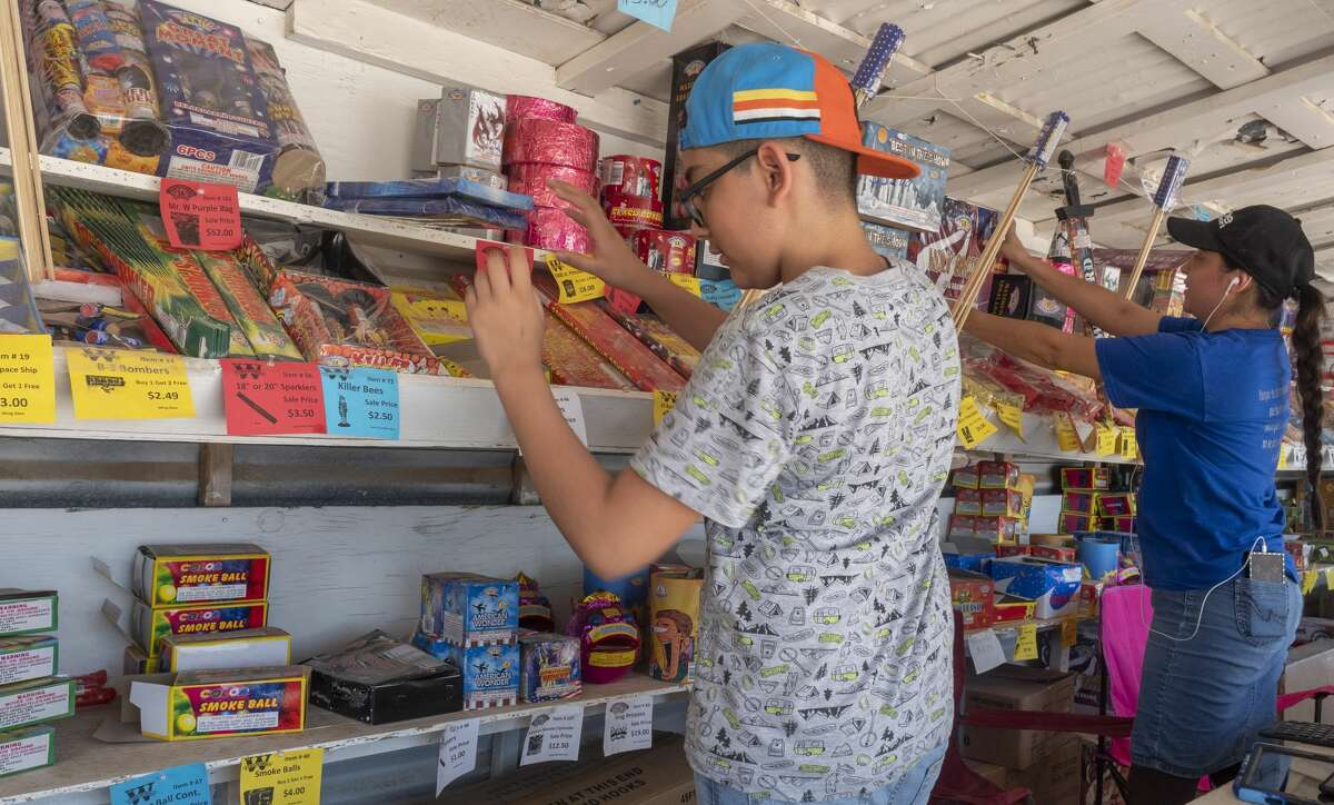 Gadiel Gomez and his mother, Thanya Gomez, organize the shelves 06/30/2020 at their Mr. W's Fireworks stand on S. Midkiff and CR 114. They and others are manning the stand as a fundraiser for their church, Apostolic Church of the Faith in Jesus Christ. Tim Fischer/Reporter-Telegram
