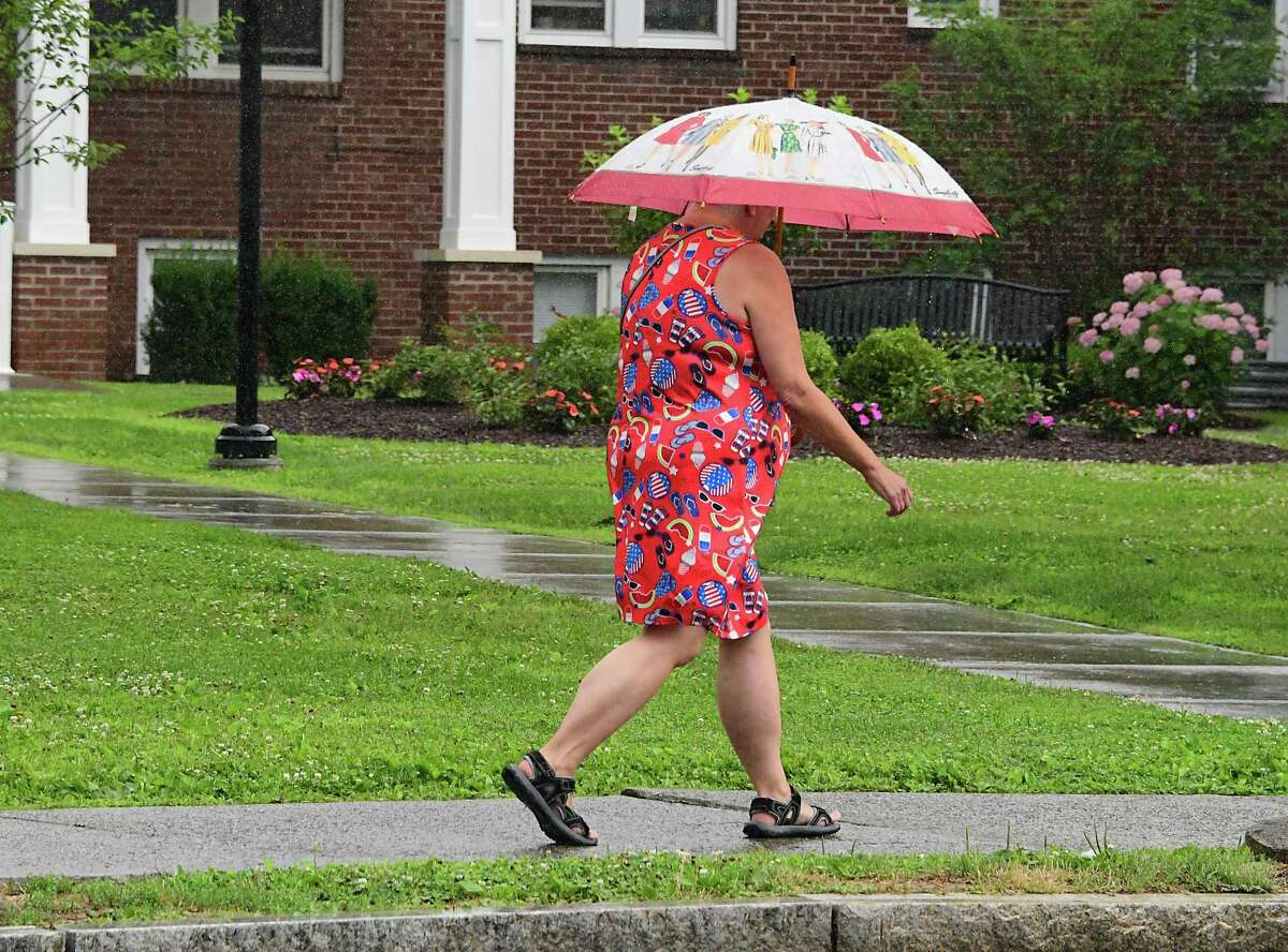 A woman uses an umbrella during a brief rain shower as she walks along New Scotland Ave. on Wednesday, July 1, 2020 in Albany, N.Y. (Lori Van Buren/Times Union)