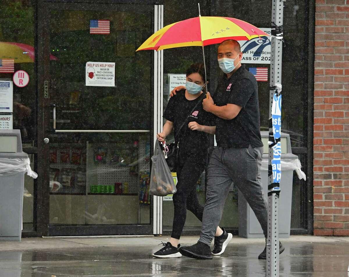 Pedestrians use an umbrella during a brief rain shower as they walk on a sidewalk along New Scotland Ave. on Wednesday, July 1, 2020 in Albany, N.Y. (Lori Van Buren/Times Union)