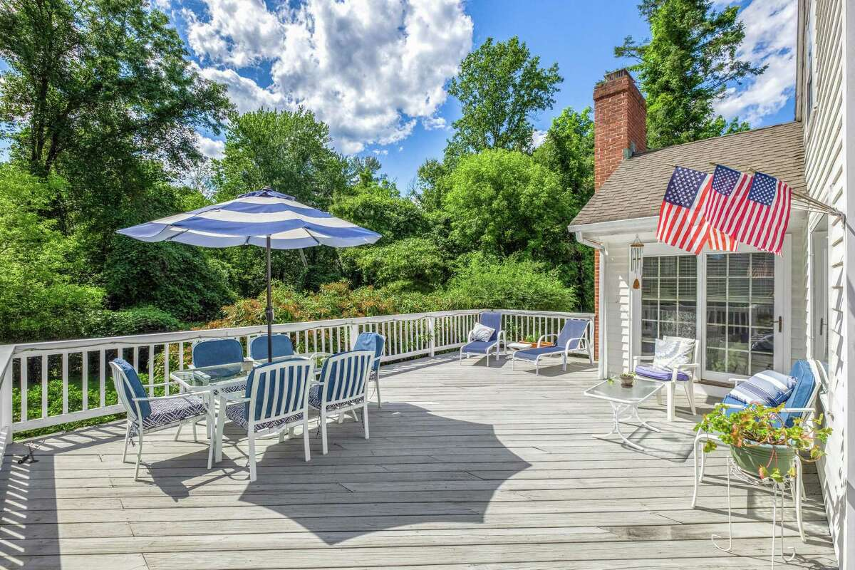 American flags decorate the front entrance and back deck of this house because the most recent owner, the late Anne Beers, was a U.S. Navy veteran and a patriot. According to Janet Beers, her mother served as a pharmacist mate in the U.S. Navy and when she was discharged in 1946, she went to Tufts University. Additionally, Janet Beers said, her mother marched in every Westport's Memorial Day parade wearing the exact uniform she wore in the service. She was honored at Town Hall the year before her passing at age 94. The nine-room, 3,236-square-foot white house with green shutters sits on a property of just over one level acre in a very convenient location in the Greens Farms neighborhood, within easy walking distance of Greens Farms Elementary School, and shops and restaurants on the Post Road (Route 1).