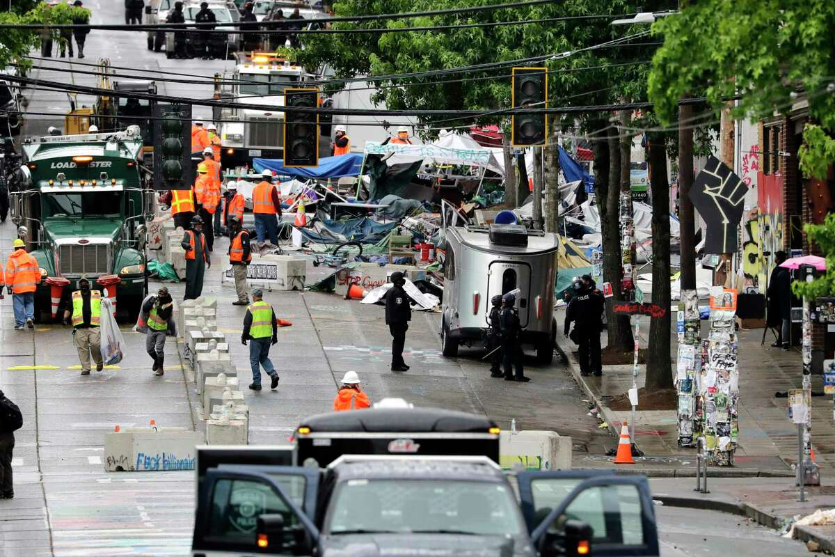 Police and city workers fill a street occupied hours earlier by an encampment of protesters Wednesday, July 1, 2020, in Seattle, where streets had been blocked off in an area demonstrators had occupied for weeks. Seattle police showed up in force earlier in the day at the