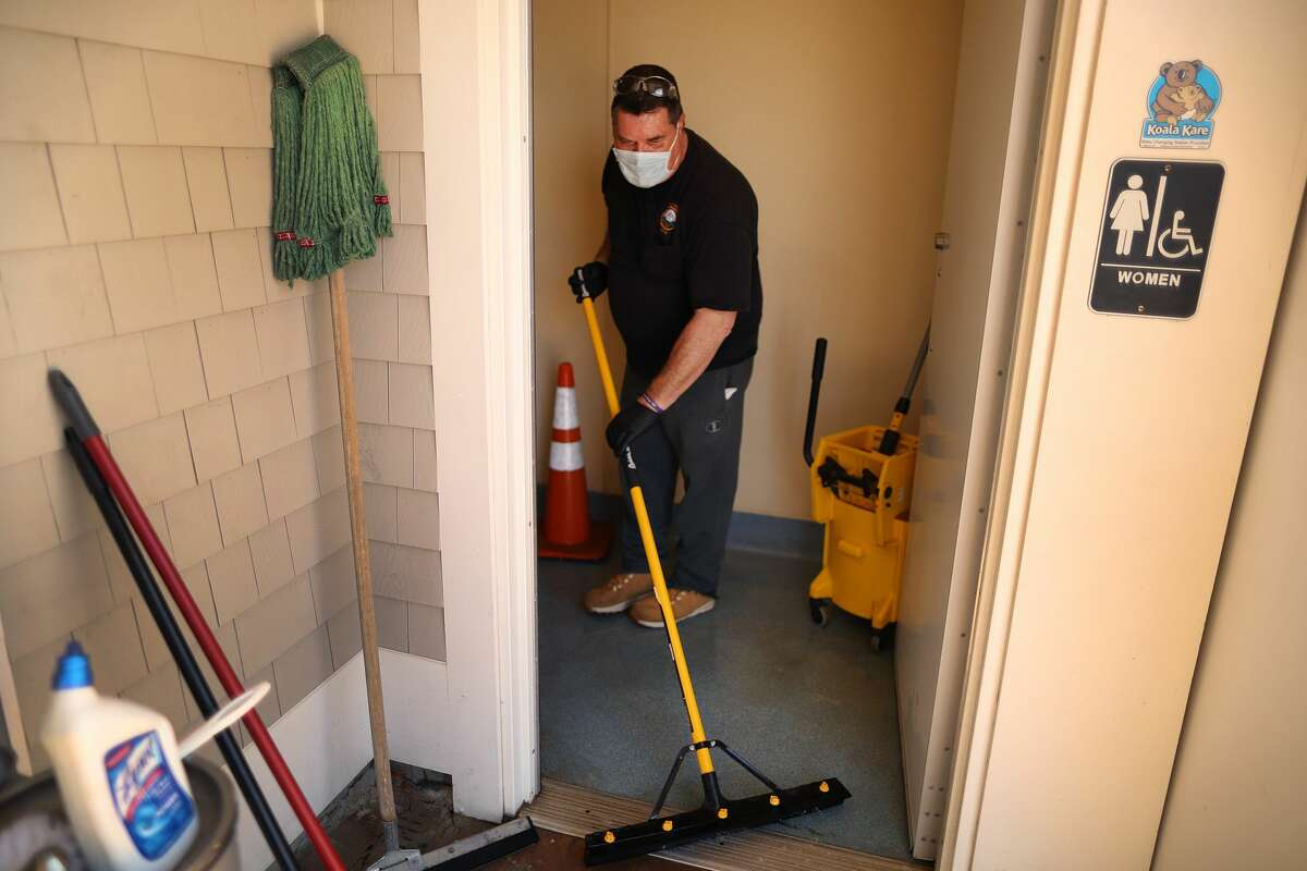 A recent study suggesting that the coronavirus could potentially spread through aerosol droplets rising from a toilet flush has led some to fear using public restrooms. Pictured: A Department of Public Works worker washes the floor of the public women's room at Mayflower Beach, and also disinfects it with cleaner as he helps to get the the restrooms open for the season in Dennis, MA on May 13, 2020.