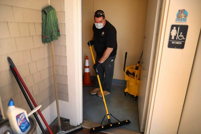 Dennis DPW worker Steve Crowley washed the floor of the public women's room at Mayflower beach, and also disinfected it with cleaner as he helped to get the the restrooms open for the season in Dennis, MA on May 13, 2020. For now, the unseasonably cool weather has dissuaded the cooped-up masses from descending upon Cape beaches, but with warmer weather on the horizon and Memorial Day weekend just over a week away, anxiety is mounting. Town managers contend that beaches will operate differently but struggle when pressed on specifics. Most officials on the Cape are looking to Governor Charlie Baker to institute guidelines on how to manage anticipated beach crowds, but so far the state has not provided town managers with guidelines or an assurance that theyll come before June.
