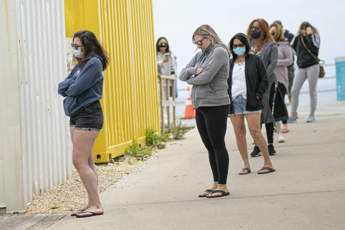 People wait in line for the restroom by the boardwalk in Asbury Park, New Jersey on May 24, 2020.