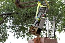A forklift lifts the statue from it pedestal.