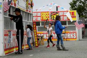 SAN BRUNO, CA - JUNE 30: A young girl waves an American flag as customers purchase fireworks from fireworks stands outside of The Shops at Tanforan on June 30, 2017 in San Bruno, California. San Francisco Bay Area fire departments are on heightened alert as vendors in select Bay Area counties sell fireworks ahead of the Fourth of July holiday. (Photo by Justin Sullivan/Getty Images)