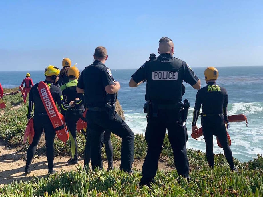 Santa Cruz police officers and rescue swimmers survey the scene Tuesday, June 30, 2020, where a carjacking suspect drove a stolen vehicle over a cliff on West Cliff Drive. The suspect survived. Photo: Santa Cruz Police Department
