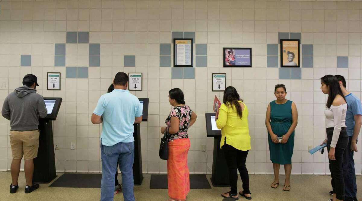 People get number tickets from the electronic kiosks in the lobby of a Texas Department of Public Safety Driver License Mega Center at South Gessner Road on Friday, Aug. 23, 2019, in Houston. Long DPS lines are a thing of the past as state officials reopen offices by appointment.