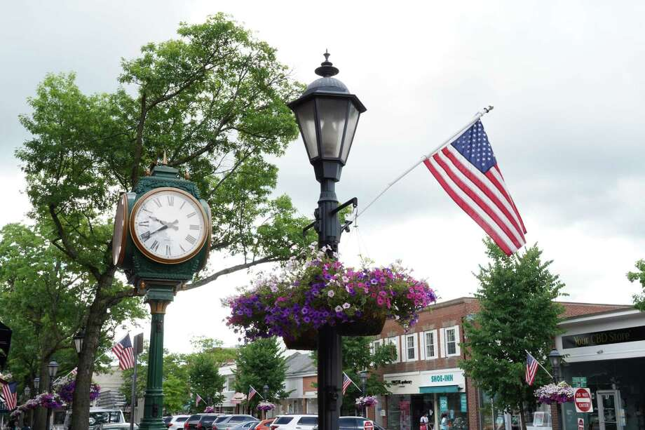 """In keeping with tradition, flags wave on Elm Street in New Canaan. The song, """"God Bless America,"""" was recently sung by rising New Canaan High School senior Megan Lydon before a 24-minute video of the town's 2019 celebration, and firework display, on the town's television station, NCTV79, (Channel 79). The presentation was shown on the hour at 3 p.m., 5 p.m., 7 p.m., and 9 p.m., on Friday, July 3, 2020, and Saturday, July 4, 2020. The fireworks are still able to be watched online via the video-sharing platform Vimeo. The flags are going to remain up at various locations throughout the town through Labor Day as they were the previous year. Photo: Grace Duffield / Hearst Connecticut Media"""