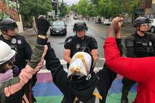 Protesters stand holding up their arms in front of a road blocked by police in the Capitol Hill Organized Protest zone early Wednesday, July 1, 2020, in Seattle. Police in Seattle have torn down demonstrators' tents in the city's so-called occupied protest zone after the mayor ordered it cleared. (AP Photo/Elaine Thompson)