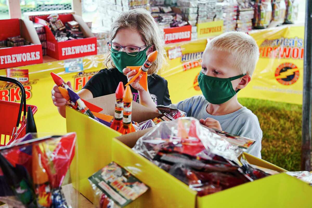 Children wear face masks as they pick out fireworks at Wild Willy's Fireworks tent in Omaha, Neb., Monday, June 29, 2020, ahead of the 4th of July holiday,