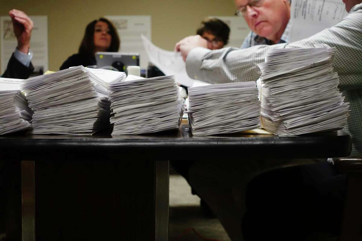 Stacks of absentee ballots are seen on a table as employees of the Rensselaer County Board of Elections begin the task of counting them on Wednesday, July 1, 2020, in Troy, N.Y. (Paul Buckowski/Times Union)