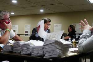 Robert Harding, center, representing Assemblyman John McDonald III, looks over absentee ballots as employees of the Rensselaer County Board of Elections began counting the ballots on Wednesday, July 1, 2020, in Troy, N.Y. Assemblyman McDonald is running against Sam Fein in the 198th Assembly District race.    (Paul Buckowski/Times Union)