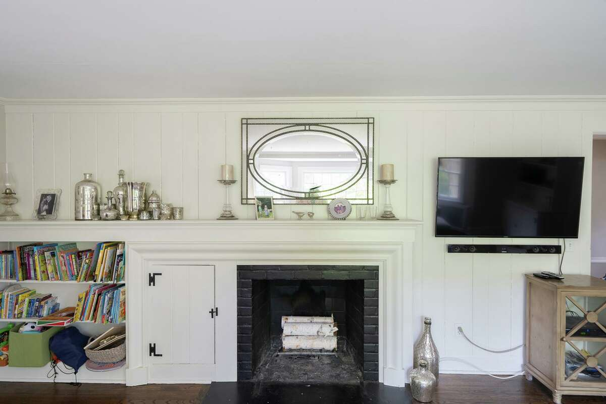 Against a wood paneled wall in the formal living room there is a fireplace and built-ins.