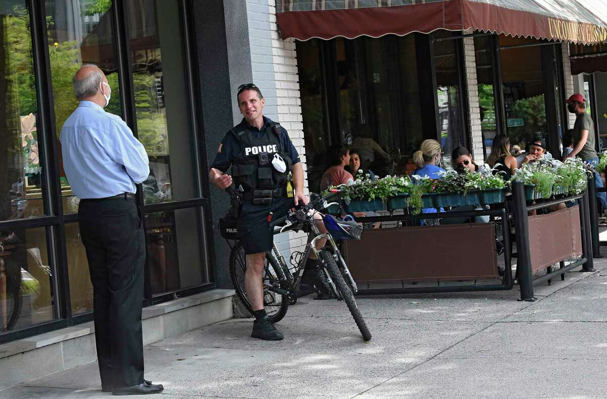 A police officer is seen chatting with a man on Broadway on Wednesday, July 1, 2020 in Saratoga Springs, N.Y. (Lori Van Buren/Times Union)