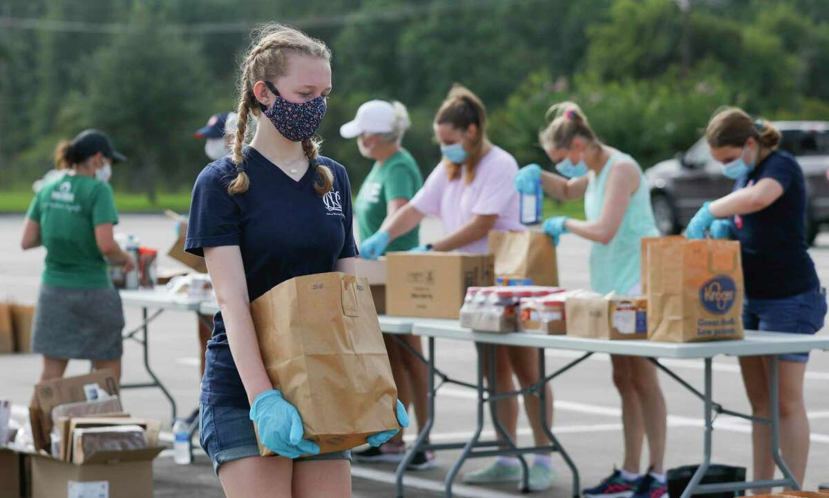 Sami Whitehead carries a bag ful of groceries as Community Assistance Center and Interfaith of The Woodlands host a mobile food pantry for 600 families at Woodforest Bank Stadium, Wednesday, July 1, 2020, in Shenandoah.