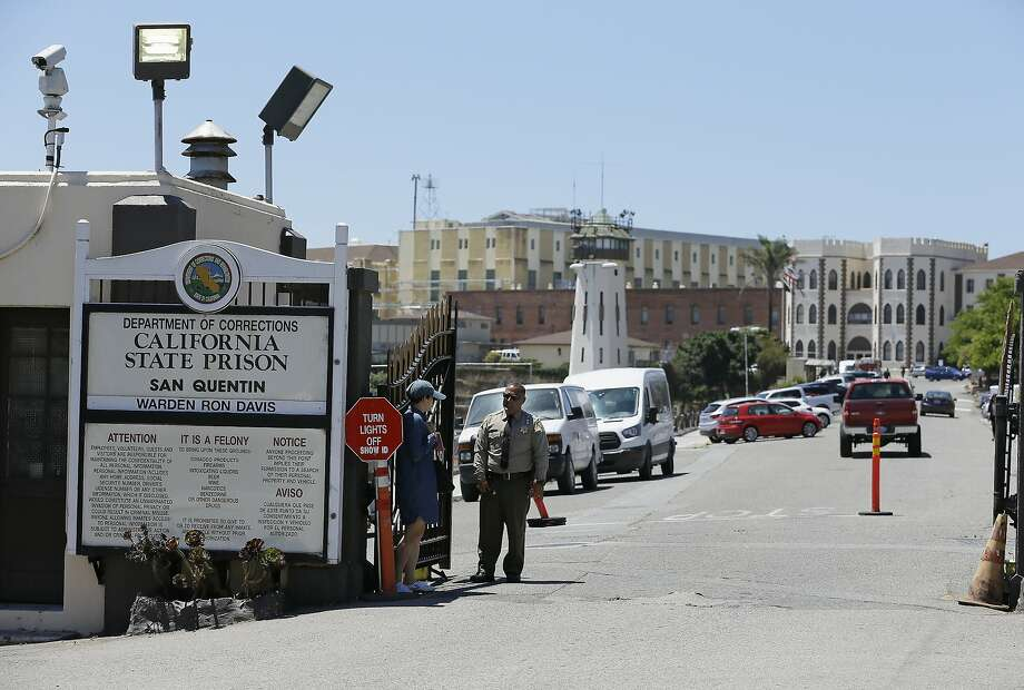 "FILE - A Department of Corrections officer guards the main entryway leading into San Quentin State Prison in San Quentin, Calif., July 24, 2019. California lawmakers harshly criticized state corrections officials Wednesday, July 1, 2020, for a ""failure of leadership"" for botching their handling of the pandemic by inadvertently transferring infected inmates to an untouched prison, triggering the state's worst prison coronavirus outbreak. A third of the 3,500 inmates at San Quentin State Prison near San Francisco have tested positive since officials transferred 121 inmates from the heavily impacted California Institution for Men in Chino on May 30 without properly testing them for infections. (AP Photo/Eric Risberg, File) Photo: Eric Risberg / Associated Press 2019"