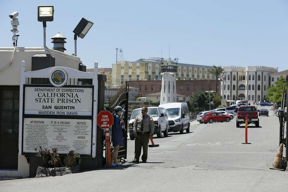 "FILE - A Department of Corrections officer guards the main entryway leading into San Quentin State Prison in San Quentin, Calif., July 24, 2019. California lawmakers harshly criticized state corrections officials Wednesday, July 1, 2020, for a ""failure of leadership"" for botching their handling of the pandemic by inadvertently transferring infected inmates to an untouched prison, triggering the state's worst prison coronavirus outbreak. A third of the 3,500 inmates at San Quentin State Prison near San Francisco have tested positive since officials transferred 121 inmates from the heavily impacted California Institution for Men in Chino on May 30 without properly testing them for infections. (AP Photo/Eric Risberg, File)"