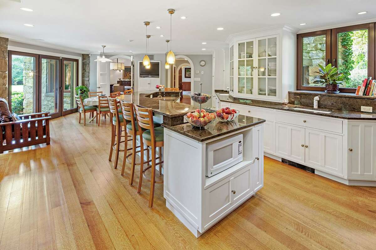 The sizable gourmet eat-in kitchen features a long two-tiered center island with a breakfast bar for six, glass-front cabinetry and sliding doors in the casual dining area to the terrace.