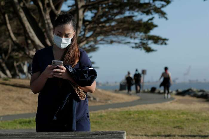 Lauren Holladay wearing a surgical mask at the Emeryville Marina in Emeryville, Calif., on Tuesday, June 30, 2020. As more positive test results show a spike in the coronavirus infections, people wanting to get outside are wearing masks to prevent the spread of the disease.