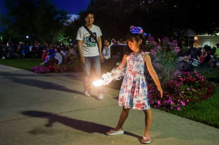 A young girl plays with a sparkler near Dow Diamond last year, where thousands of people gathered near Dow Diamond to watch fireworks last July 4. (Daily News File Photo)