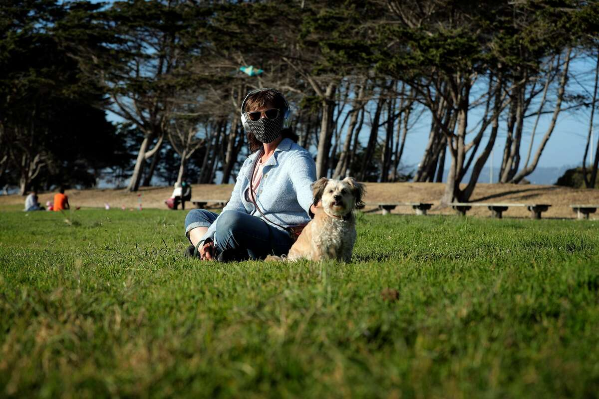 Marylee Cabrera with her dog wearing a mask at the Emeryville Marina in Emeryville, Calif., on Tuesday, June 30, 2020. As more positive test results show a spike in the coronavirus infections, people wanting to get outside are wearing masks to prevent the spread of the disease.