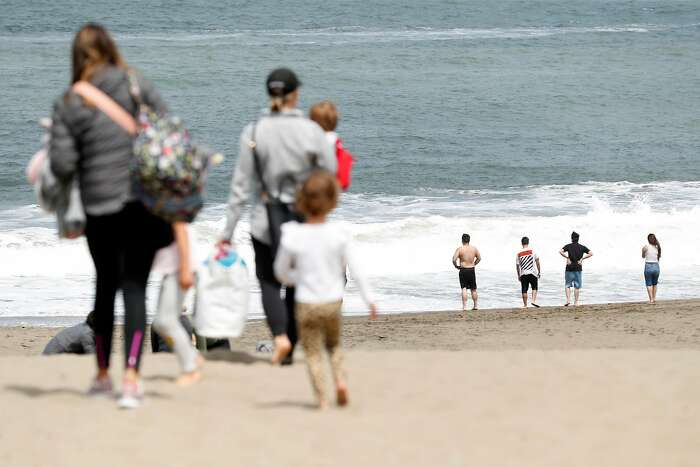 People recreate at Baker Beach in San Francisco, Calif., on Wednesday, July 1, 2020. There will be no official fireworks' displays this 4th of July weekend, but BBQing, road trips, camping and beach-going will be popular activities.