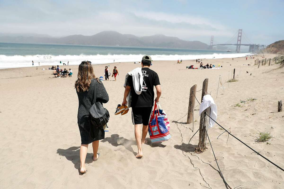 Michael Rea and Angel Mendoza of Vallejo arrive to spend the afternoon at Baker Beach in San Francisco, Calif., on Wednesday, July 1, 2020. There will be no official fireworks' displays this 4th of July weekend, but BBQing, road trips, camping and beach-going will be popular activities.