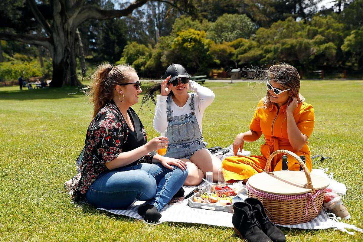 (left to right) Celeste Sexton, Luz Jaimes and Jude Viramontes enjoy a picnic in Golden Gate Park in San Francisco, Calif., on Wednesday, July 1, 2020. There will be no official fireworks' displays this 4th of July weekend, but BBQing, road trips, camping and beach-going will be popular activities.