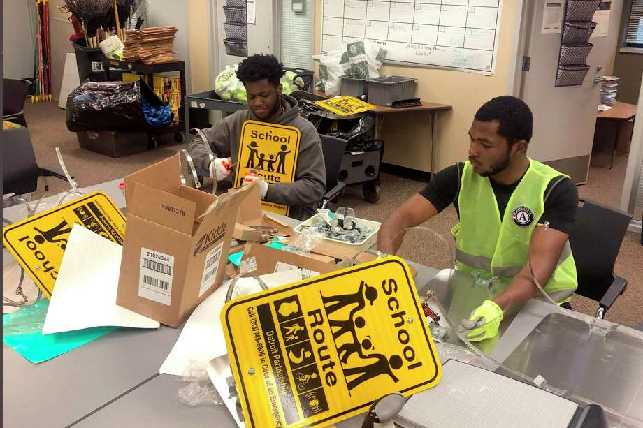 Nicholas Thomas, left, and Joe Wright, right, prepare school safety signs as part of the AmeriCorps Urban Safety Program at Wayne State University's Center for Urban Studies on Jan. 16. Connecticut's new ConnectiCorps, modeled after the federal AmeriCorps, will give employment to youth at nonprofits which are short on volunteers since the coronavirus pandemic. Photo: Corey Williams / Associated Press / Copyright 2020 The Associated Press. All rights reserved.