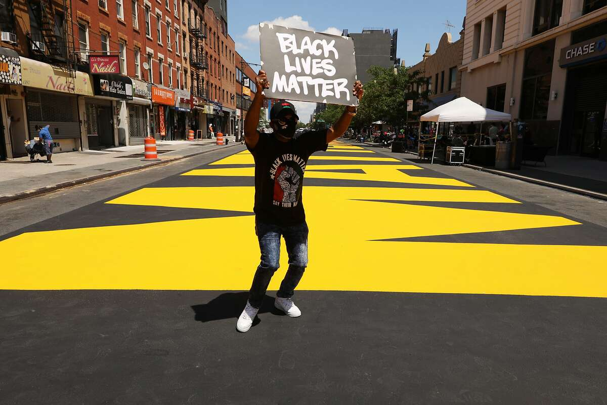 NEW YORK, NEW YORK - JUNE 29: A man dances on a massive Black Lives Matter mural covers a city street on June 29, 2020 in the Brooklyn borough of New York City. The mural, which was painted over the weekend, runs along the block of Fulton Street between Marcy and Brooklyn avenues. The street will become a pedestrian-only plaza for the duration of the summer. (Photo by Spencer Platt/Getty Images)