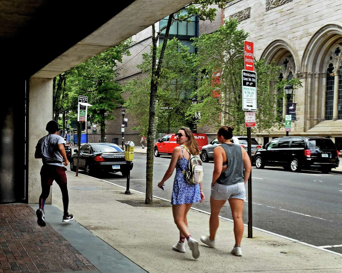 New Haven, Connecticut - Wednesday, July 1, 2020: A jogger and pedestrians pass by the Yale Center for British Art as they travel up Chapel Street near High Street in New Haven.