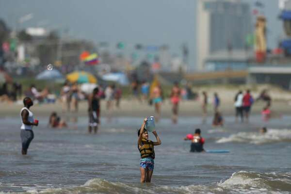 People enjoy the weather at the beach near the Seawall on Sunday, May 24, 2020, in Galveston, Texas.