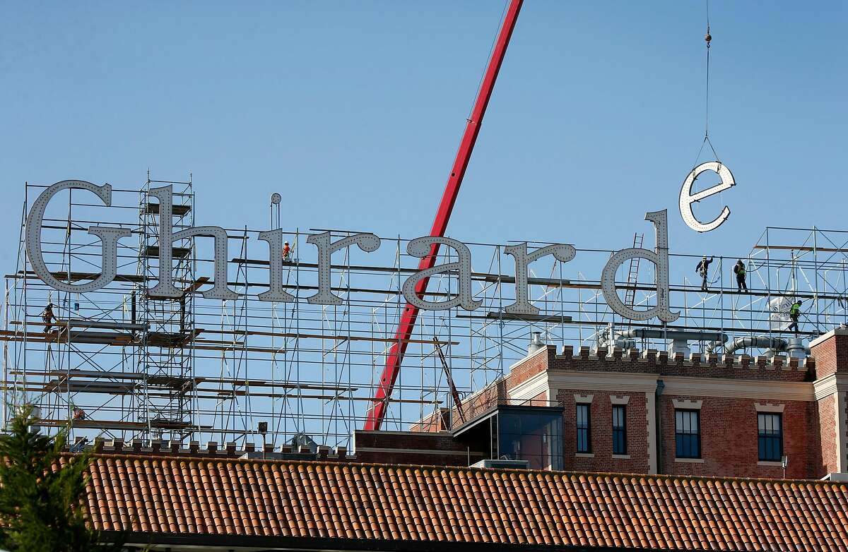 The iconic sign above Ghirardelli Square is removed one letter at a time in San Francisco, Calif. on Wednesday, July 1, 2020. The aging illuminated characters will be replicated and replaced with new ones.