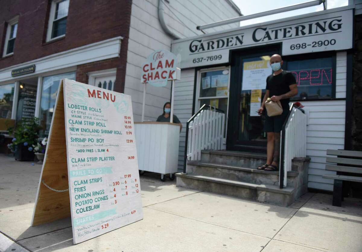 A large menu is displayed on the sidewalk outside Garden Catering in Old Greenwich, Conn. Wednesday, July 1, 2020.