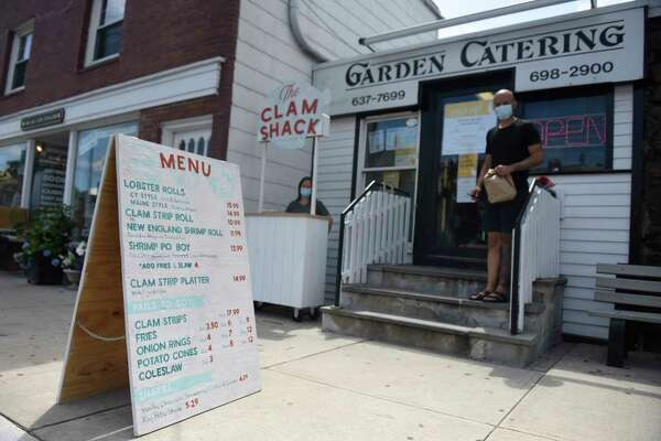 A large menu is displayed on the sidewalk by the new Clam Shack outside Garden Catering in Old Greenwich, Conn. Wednesday, July 1, 2020. The outdoor stand will be open Thursdays through Sundays in the summer, serving a variety of seafood and fried food.