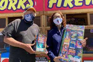 (Left to right) Greg Pierce, incoming San Bruno Rotary Club President and Barbara Einsiedl, outgoing Rotary Club President, stand holding fireworks outside a Phantom Fireworks booth selling legal fireworks in San Bruno Calif. on June 30, 2020. Proceeds from the fireworks sales goes to the San Bruno Rotary Club.