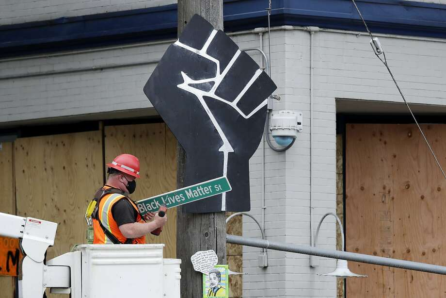 """A worker removes a """"Black Lives Matter St."""" sign from a Seattle police precinct Wednesday, July 1, 2020, in Seattle, where streets had been blocked off in an area demonstrators had occupied for weeks. Seattle police showed up in force earlier in the day at the """"occupied"""" protest zone, tore down demonstrators' tents and used bicycles to herd the protesters after the mayor ordered the area cleared following two fatal shootings in less than two weeks. The """"Capitol Hill Occupied Protest"""" zone was set up near downtown following the death of George Floyd while in police custody in Minneapolis. Photo: Elaine Thompson, Associated Press"""
